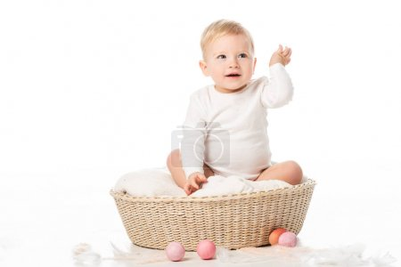 Photo for Child with raised hand sitting on blanket in basket with Easter eggs around on white background - Royalty Free Image