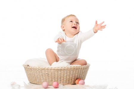 Photo for Cute child with outstretched hands and open mouth sitting in basket on white background - Royalty Free Image