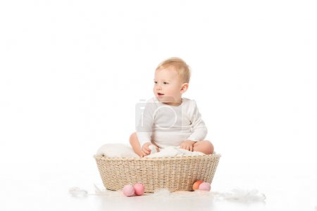 Photo for Child with open mouth looking away, sitting in basket next to Easter eggs on white background - Royalty Free Image