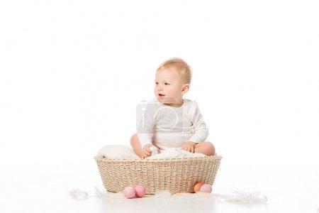 Photo pour Enfant à bouche ouverte regardant ailleurs, assis dans le panier à côté des œufs de Pâques sur fond blanc - image libre de droit