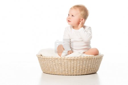 Photo for Child touching ear and looking away, sitting on blanket in basket on white background - Royalty Free Image