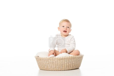 Photo for Cute boy with open mouth sitting on blanket in basket on white background - Royalty Free Image