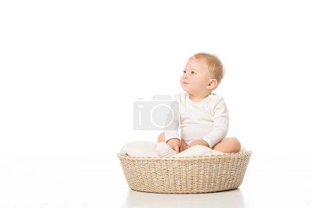 Photo pour Mignon enfant regardant loin et assis sur la couverture dans le panier sur fond blanc - image libre de droit