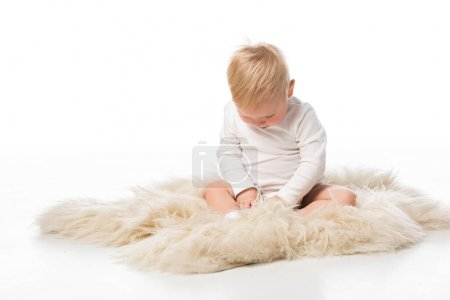 Photo for Cute child with lowered head sitting on fur on white background - Royalty Free Image