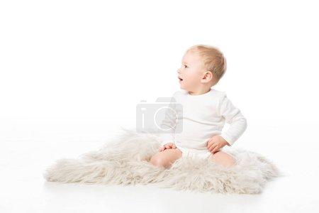 Photo pour Enfant mignon regardant loin avec la bouche ouverte et assis sur la fourrure sur fond blanc - image libre de droit
