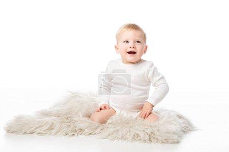Photo pour Mignon enfant heureux levant les yeux avec la bouche ouverte et assis sur la fourrure sur fond blanc - image libre de droit