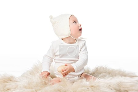 Photo pour Enfant portant un bonnet bébé, tenant un oeuf de Pâques, regardant loin avec la bouche ouverte sur la fourrure isolée sur blanc - image libre de droit