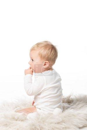 Photo pour Vue latérale de mignon enfant avec doigt dans la bouche, assis sur la fourrure isolé sur blanc - image libre de droit