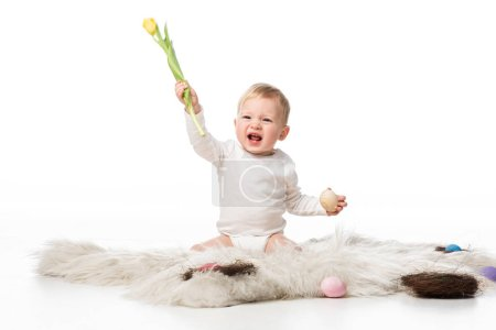 Child with open mouth holding tulip and easter egg, sitting on fur on white background