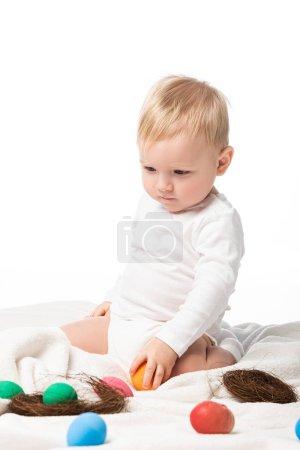 Photo pour Enfant mignon tenant oeuf de Pâques, regardant vers le bas, assis sur une couverture isolée sur blanc - image libre de droit
