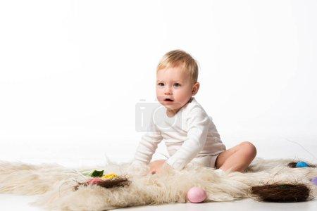 Photo pour Enfant avec la bouche ouverte, assis sur la fourrure avec les nids et les œufs de Pâques autour sur fond blanc - image libre de droit