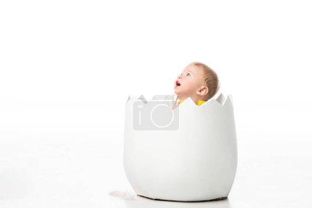 Photo pour Enfant aigu regardant vers le haut, la bouche ouverte à l'intérieur de la coquille sur fond blanc - image libre de droit