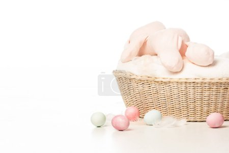Photo for Bunny on top of blanket in basket next to easter eggs on white background - Royalty Free Image