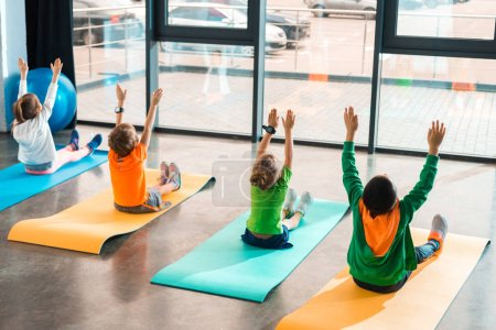 Photo pour Back view of children with hands in air working out on fitness mats in gym - image libre de droit