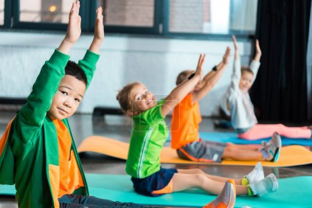 Selective focus of multiethnic children looking at camera with hands in air and working out on fitness mats in gym