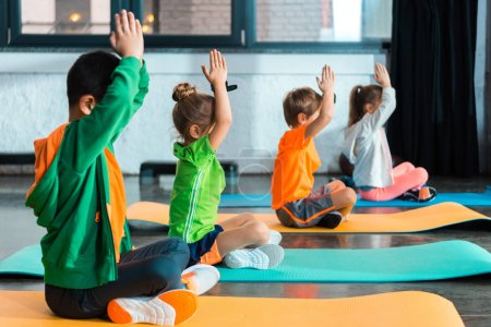 Photo for Selective focus of children with clenched hands stretching on fitness mats in gym - Royalty Free Image