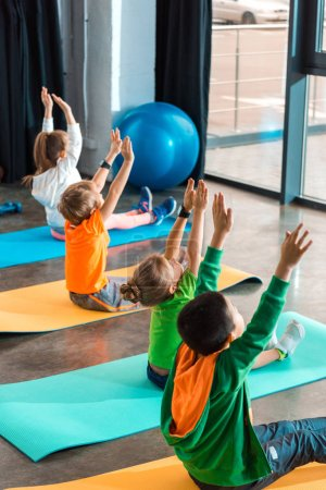 Photo pour Vue à grand angle d'enfants multiethniques les mains en l'air faisant de l'exercice sur des tapis de conditionnement physique dans un gymnase - image libre de droit