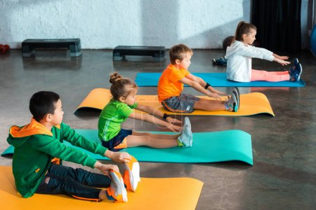 Multicultural children stretching while sitting on fitness mats in gym