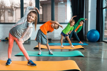 Photo for Selective focus of multicultural children warming up on fitness mats in gym - Royalty Free Image