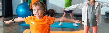 Photo pour Vue recadrée des enfants faisant de l'exercice avec les mains tendues sur les tapis de fitness, prise de vue panoramique - image libre de droit