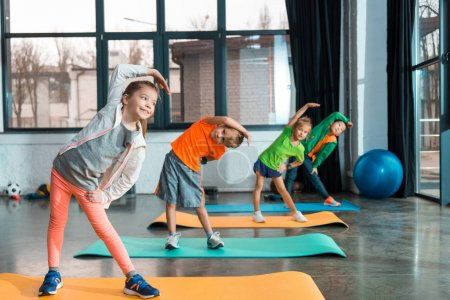 Photo for Selective focus of multicultural children warming up on fitness mats in sports center - Royalty Free Image