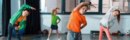 Photo for Selective focus of multicultural children warming up on fitness mats in gym, panoramic shot - Royalty Free Image