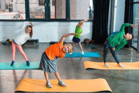 Foto de Niños multiculturales calentándose juntos en colchonetas de fitness en el gimnasio - Imagen libre de derechos