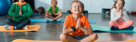 Foto de Enfoque selectivo de los niños con las manos apretadas y piernas cruzadas sobre las colchones de fitness, tiro panorámico. - Imagen libre de derechos