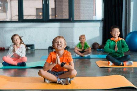 Foto de Enfoque selectivo de niños multiétnicos con manos encadenadas y piernas cruzadas sentadas sobre colchones de fitness. - Imagen libre de derechos