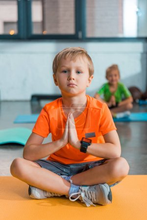 Selective focus of boy with clenched hands and crossed legs on fitness mat in sports center