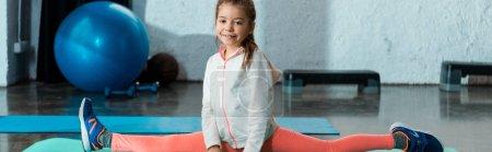 Photo pour Concentration sélective de l'enfant faisant scission dans la salle de gym, tir panoramique - image libre de droit