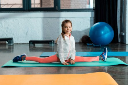 Photo pour Concentration sélective de l'enfant souriant et faisant scission sur tapis de fitness dans la salle de gym - image libre de droit
