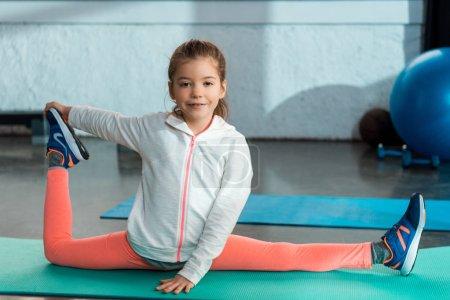 Photo pour Concentration sélective de l'enfant souriant, étirant, faisant diviser sur tapis de fitness dans la salle de gym - image libre de droit