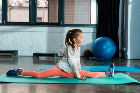 Photo pour Concentration sélective de l'enfant faisant scission sur tapis de fitness dans la salle de gym - image libre de droit