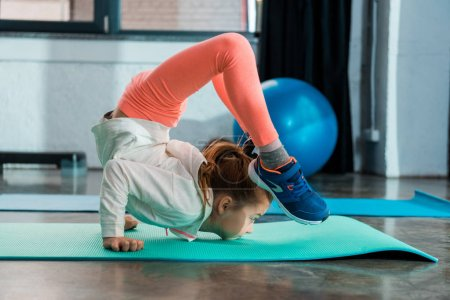 Photo for Selective focus of child stretching on fitness mat in gym - Royalty Free Image