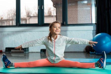 Photo pour Concentration sélective de l'enfant positif avec les mains tendues faisant diviser sur tapis de fitness dans la salle de gym - image libre de droit