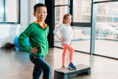 Photo for Selective focus of multicultural children with hands on hips doing exercise on step platforms in gym - Royalty Free Image