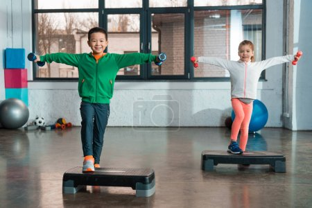Photo for Multicultural children with outstretched hands holding dumbbells and doing exercise on step platforms in gym - Royalty Free Image