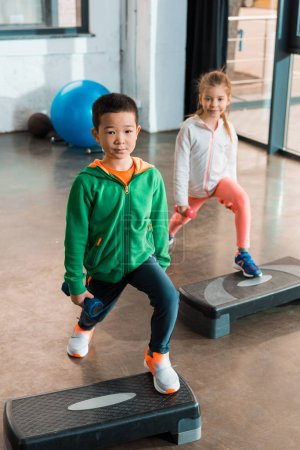 Photo for High angle view of multiethnic children holding dumbbells and working out on step platforms in gym - Royalty Free Image