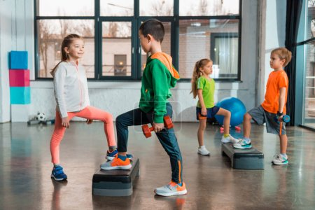 Photo for Selective focus of multiethnic children holding dumbbells and working out together on step platforms in gym - Royalty Free Image