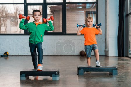 Photo for Front view of multicultural children holding dumbbells and doing Step Aerobics in gym - Royalty Free Image