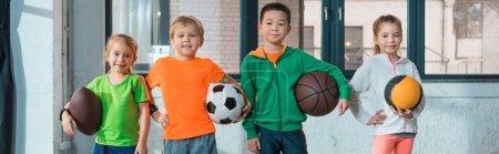 Vista frontal de niños multiculturales sosteniendo bolas y sonriendo juntos en el gimnasio, plano panorámico