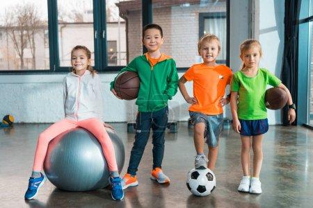 Frontansicht Kind sitzt auf Fitnessball neben multiethnischen Kindern mit Bällen in der Turnhalle