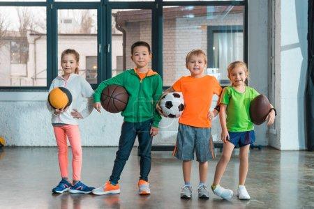 Vue de face des enfants multiethniques souriant et tenant des balles dans la salle de gym