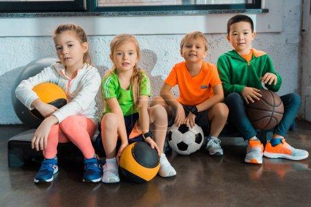 Multikulti-Kinder sitzen mit Bällen in Turnhalle auf Trittbrettern