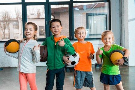 Vorderansicht glücklicher multikultureller Kinder mit Bällen in der Turnhalle