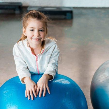 Photo pour Concentration sélective de l'enfant souriant et penché sur la balle de fitness dans la salle de gym - image libre de droit