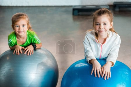 Photo for Selective focus of children looking at camera, smiling and leaning on fitness balls in gym - Royalty Free Image