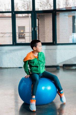Photo pour Foyer sélectif de asiatique garçon assis sur fitness ball dans gym - image libre de droit