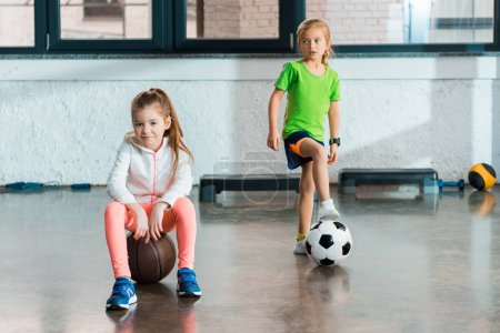 Photo for Front view of child sitting on ball next to kid putting leg on soccer-ball, looking away in gym - Royalty Free Image